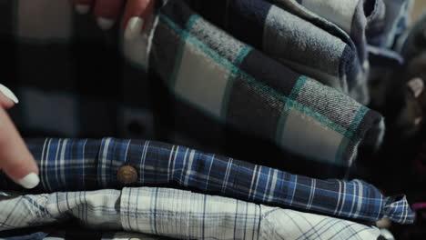 Women-s-hands-sort-through-a-stack-of-men-s-shirts-4