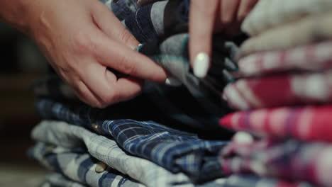 Women-s-hands-sort-through-a-stack-of-men-s-shirts-5