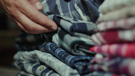 A-man-chooses-a-shirt-from-a-neat-pile