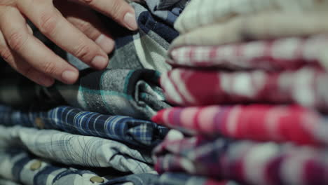 Men-s-hands-sort-clothes-in-a-stack-on-the-shelf