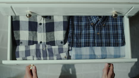 Man-opens-drawer-with-shirts