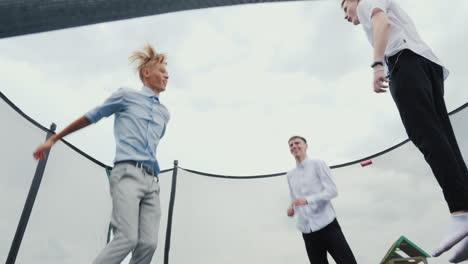 Three-high-school-graduates-jump-on-a-trampoline