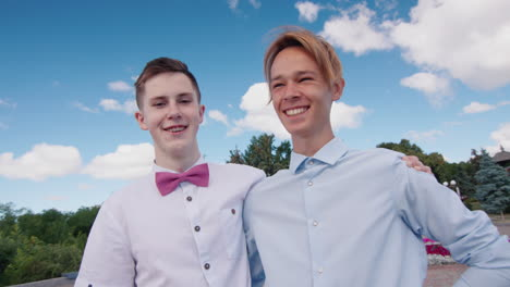 Portrait-of-two-young-high-school-graduates-smiling-and-staring-at-the-camera