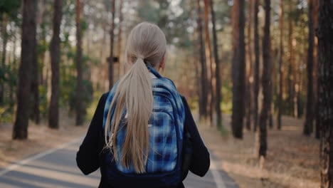 A-child-with-a-back-pack-walks-alone-through-a-park-with-tall-trees