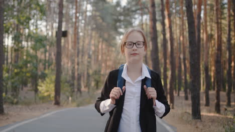 A-child-with-a-back-pack-walks-alone-through-a-park-with-tall-trees-1
