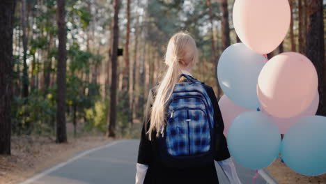 Schoolgirl-with-a-back-pack-and-balloons-walks-on-the-road-in-the-park