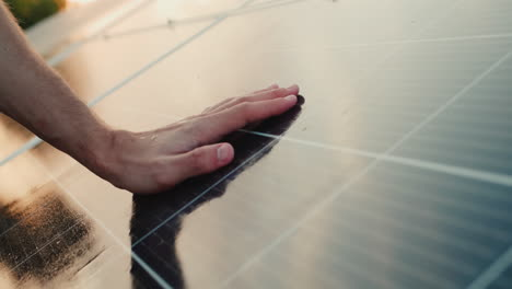 A-man-holds-his-hand-above-the-surface-of-the-solar-panels