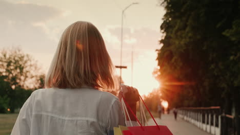 Happy-female-shopper-carries-packages-with-trendy-shopping