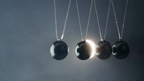 Balls-In-Newton-s-Cradle-Hit-Each-Other-In-The-Light-Of-The-Spotlight-Beam