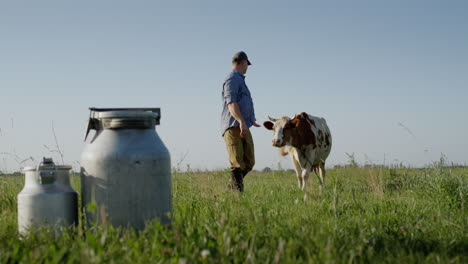 Proud-farmer-stands-in-a-pasture-where-his-cows-graze-1