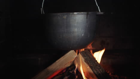 A-Pot-Hangs-In-The-Wood-Burning-Stove-The-Cook-Puts-The-Log-In-The-Fire