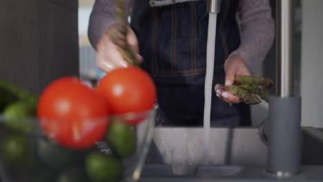 Woman-washes-asparagus