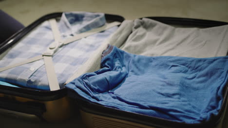 The-woman-puts-clothes-&-protective-masks-in-a-suitcase
