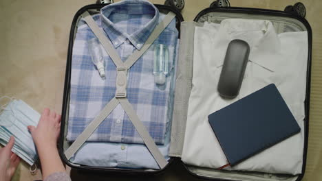 A-woman-packs-clothes-and-face-mask-for-a-business-trip-2