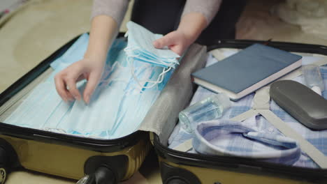 A-woman-packs-clothes-and-face-mask-for-a-business-trip-5