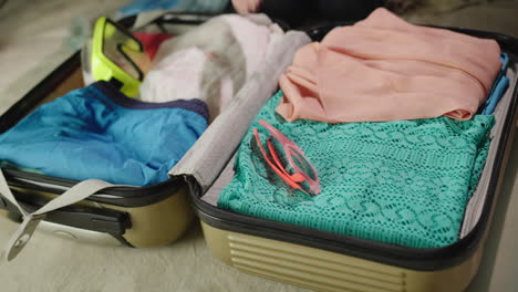 Woman-packs-clothes-for-vacation
