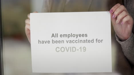 An-Employee-Hangs-An-Announcement-On-The-Door-Of-The-Establishment-That-All-Employees-Are-Vaccinated-And-Visiting-Safely