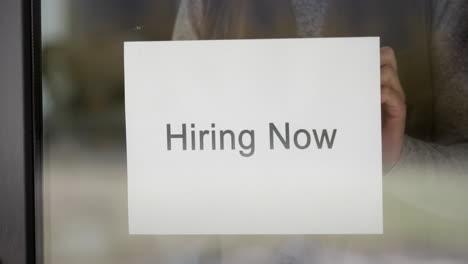 Employee-Hangs-On-The-Door-Ad-Hiring-Now