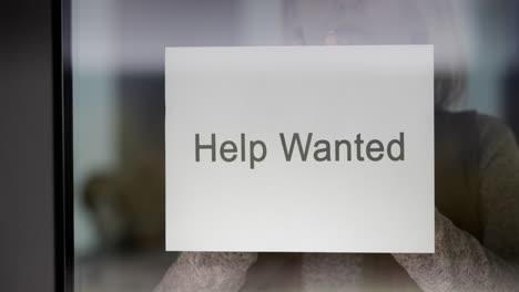 Employee-Hangs-On-The-Door-Ad-Help-Wanted