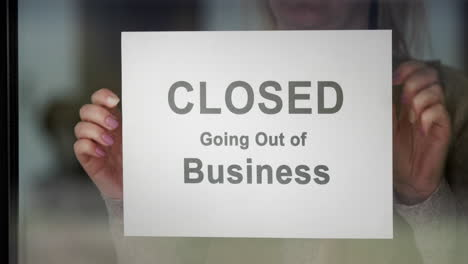 Worker-Hangs-A-Banner-Stating-Closed-Going-Out-Of-Business-On-The-Door