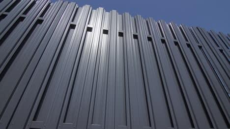 Grey-metal-fence-against-blue-sky