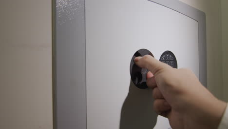 The-man-enters-the-password-on-the-door-of-the-safe-and-takes-the-gun-from-there