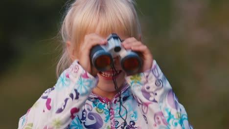 A-cheerful-child-looks-through-binoculars