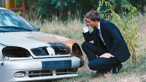 A-man-in-a-suit-inspects-a-car-after-an-accident-1