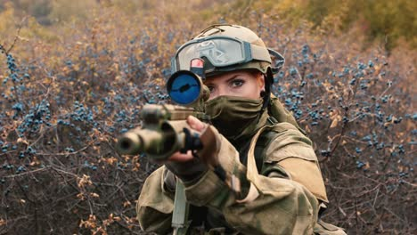 A-woman-in-camouflage-aims-with-a-rifle