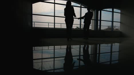 Silhouettes-of-two-businessmen-meet-in-a-spacious-hall-by-the-window