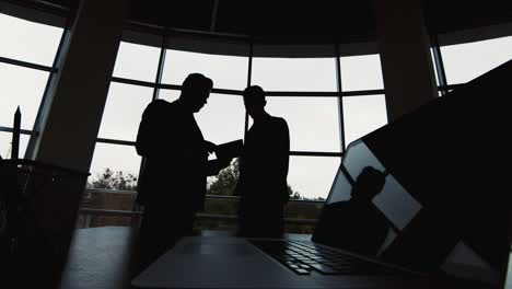 Silhouettes-of-two-businessmen-meet-in-a-spacious-hall-by-the-window-1