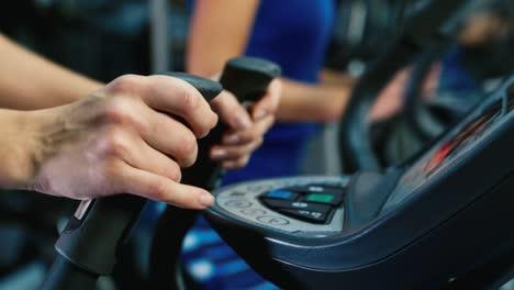 Athlete-s-hands-adjusts-the-treadmill