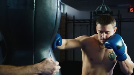 A-young-boxer-practices-punches-on-a-punching-bag
