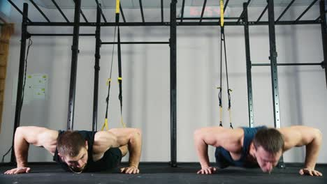 Two-athletes-do-strength-exercises-in-the-gym