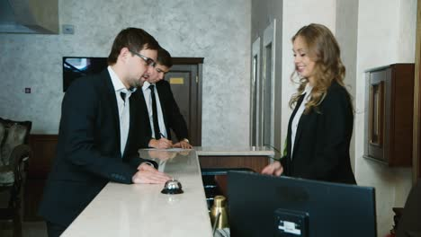 A-group-of-businessmen-fills-out-check-in-documents-1