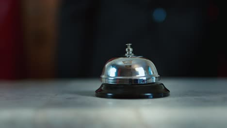 Hand-strikes-the-bell-at-the-reception-desk
