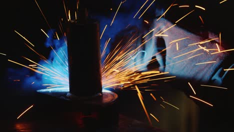 A-welder-in-a-protective-helmet-and-clothes-welds-as-sparks-fly-2