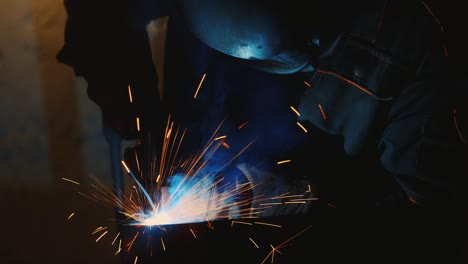 A-welder-in-a-protective-helmet-and-clothes-welds-as-sparks-fly-4