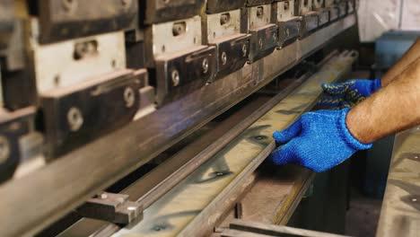 Worker-puts-a-metal-workpiece-in-a-machine-1