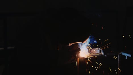 A-welder-in-a-protective-helmet-and-clothes-welds-as-sparks-fly-5