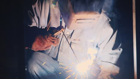 A-welder-in-a-protective-helmet-and-clothes-welds-as-sparks-fly-6