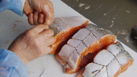 A-worker-slices-pieces-of-salmon-in-a-canned-food-factory-2
