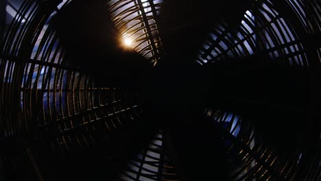 Rays-of-light-shine-through-the-blades-of-a-rotating-industrial-fan-2