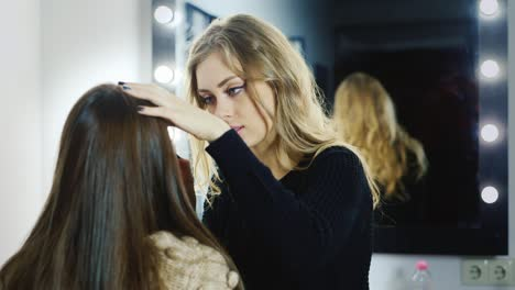 Makeup-artist-does-a-young-woman's-make-up-in-studio-4
