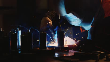 A-welder-in-a-protective-helmet-and-clothes-welds-as-sparks-fly-8