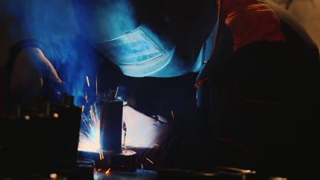 A-welder-in-a-protective-helmet-and-clothes-welds-as-sparks-fly-10