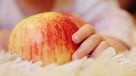 The-baby-s-hand-holds-a-large-red-apple-that-lies-on-the-floor