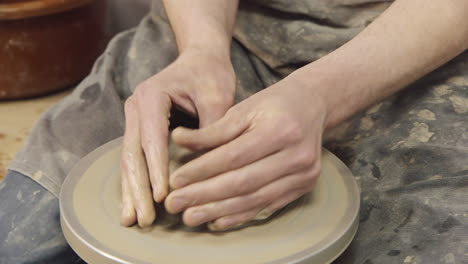 The-hands-of-a-potter-make-a-jug-on-a-potter-s-wheel
