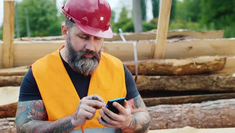 A-bearded-builder-in-a-helmet-uses-a-smartphone