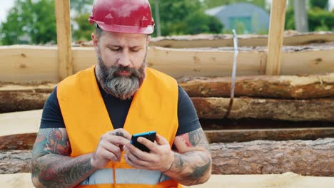 A-bearded-builder-in-a-helmet-uses-a-smartphone-1